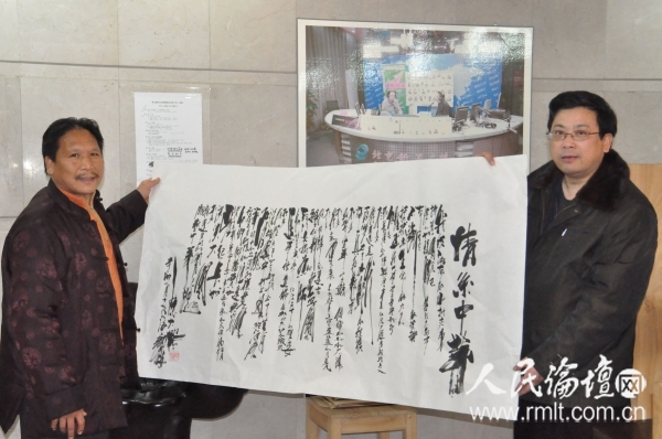 陈大鹏(左)向人民论坛网副总编辑吴礼明(右)展示他创作并书写的《情系中华》小诗  陈宇光  摄