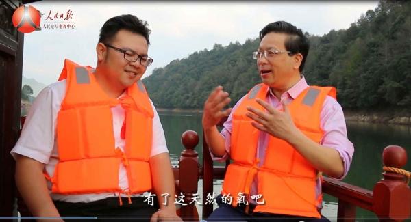 人民日报人民论坛电视主持人吴礼明博士(右) 在鸳鸯湖里游船上采访江西婺源鸳鸯湖旅游开发有限公司总经理赖建名(左) 。