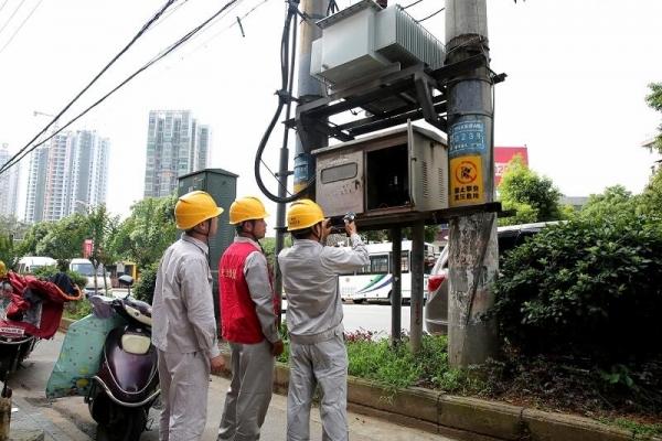 供电公司员工通过红外测温仪检测10千伏高桥A线023号杆配电变压器温度,查找故障隐患。