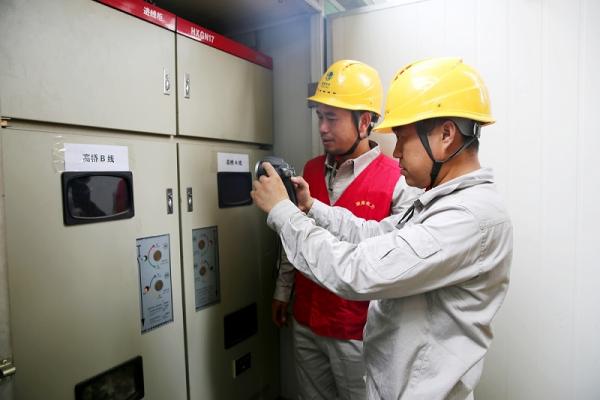 供电公司员工通过红外测温仪检测衡阳市第八中学箱式配电变压器温度,查找故障隐患,确保高考期间安全稳定供电