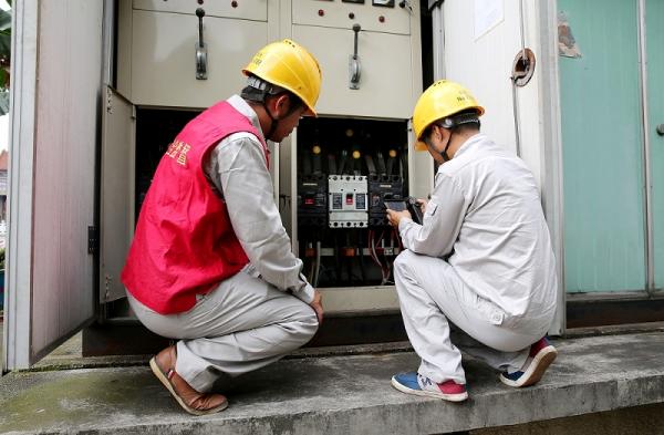 供电公司员工通过红外测温仪检测衡阳市第八中学箱式配电变压器温度,查找故障隐患